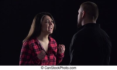 Couple quarrels and shouts on black background Slow motion -...