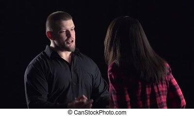 Emotional man with woman says irritably on black background. Slow motion
