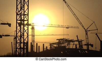 Silhouettes of cranes and construction site against orange...