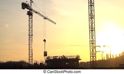 Silhouettes of crane transferring concrete plate and...
