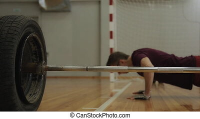 Athlet pushes up from wooden floor near the barbell - Young...