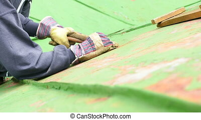 Worker Scraping off Green Paint - Worker sitting on the roof...