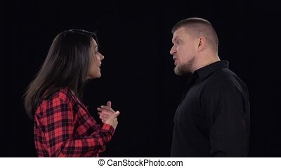 Emotional showdown between couple. Isolated on black background. Slow motion
