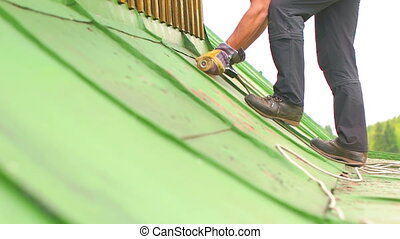 Man Working on the Roof, Sandering Paint - Construction...