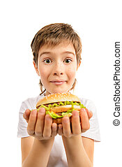 hearty meal - Happy nine year old boy eating burger with...