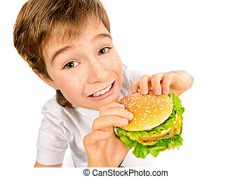 fastfood burger - Happy nine year old boy eating burger with...
