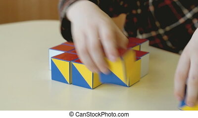 Child collecting a pattern using colored cubes