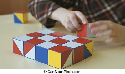 Boy collecting a pattern using colored cubes - Little boy...