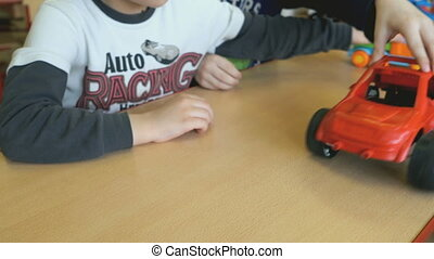 Two kids playing toy model cars at the table at the nursery