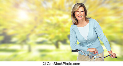 Beautiful elderly woman with bicycle. - Beautiful senior...