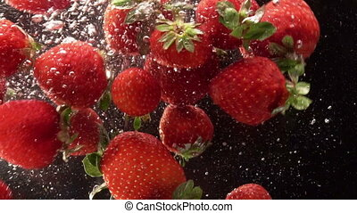 strawberries falling into the water on a black background