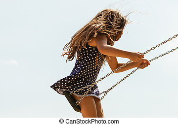 Girl swinging on swing-set - Have fun and leisure concept...