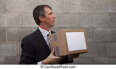Businessman Passes Box to Viewer - Businessman waiting in a...