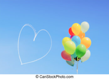 Defocused background of balloons and heart written in the sky