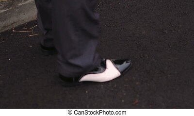 Male Feet in Black Shining Leather Shoes Standing on Asphalt Pavement