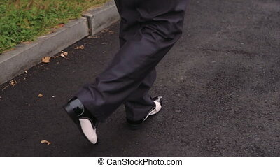Male Feet in Black Shining Leather Shoes Stepping on Asphalt Pavement