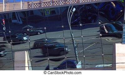 Deformed urban traffic reflections in mirror front of modern...