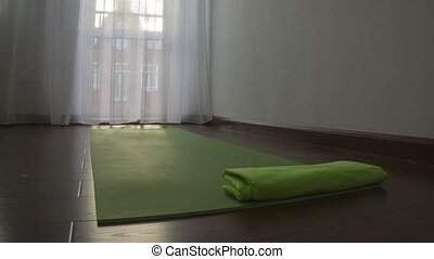 Green yoga mat and towel in sunny room. Day and night time...