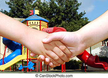 children shaking hands - two children shaking hands in front...