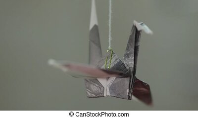 Paper origami crane rotating on thread against gray...