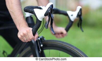 Sportsman grips handlebar of road bicycle. Racking focus...