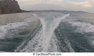 Trail on sea surface behind fast moving motor boat
