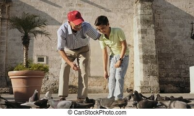 3-Grandparent And Grandson Feeding Pigeons With Bread On...