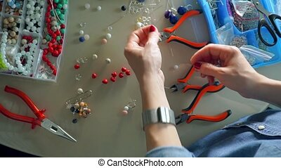 Work place of accessories artist making bead earrings, view...