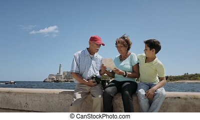 8-Family Grandparents Reading Tourist Map In Habana Cuba