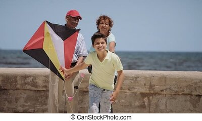 13-Family Boy And Grandparents Flying Kite Near Sea...