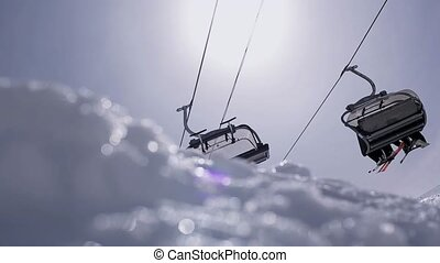 Ski resort. View of ski lifts. Snowboarders and skiers. Blue sky. Sunny day.