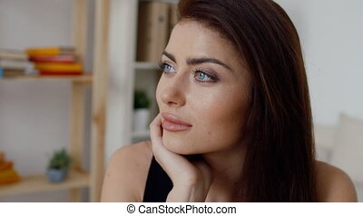 Portrait of confident businesswoman with hand on cheeks looking away in office