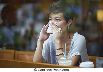 a sick young woman blowing her nose