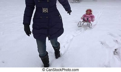 Mother pull daughter baby on sledge along snow in winter...