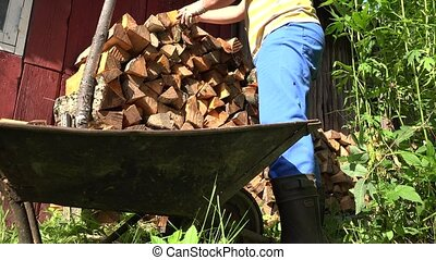 Male gardener hands with gloves unload chopped wood firewood from cart. 4K