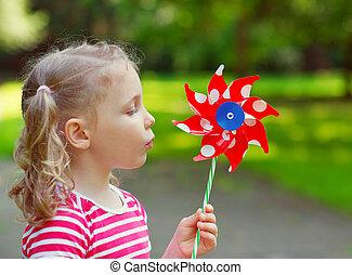 Pretty little girl holds windmill in hand - Pretty little...