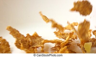 Golden corn flakes scattering on white plate macro super...