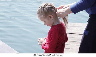 Mother girl braids hair on nature
