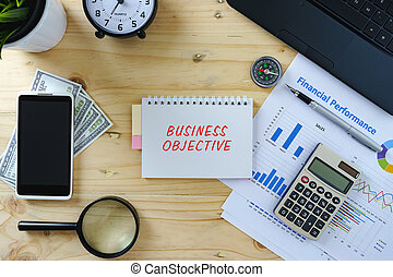 Business concept.Top view of working table with laptop, calculator, chart, smartphone, magnifying glass, clock, compass, pen and banknotes.Word BUSINESS OBJECTIVE written on notepad.