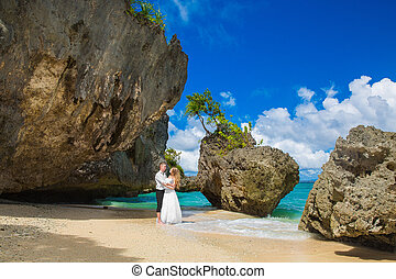 Happy Bride and Groom having fun on the tropical beach...