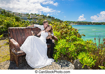 Happy bride and groom sitting on the bench in front of...