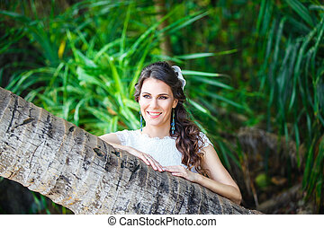 Close-up portrait young beautiful bride in a tropical jungle...