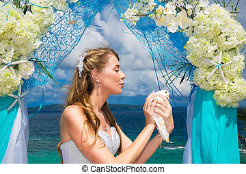 The happy bride with white doves on a tropical beach under...