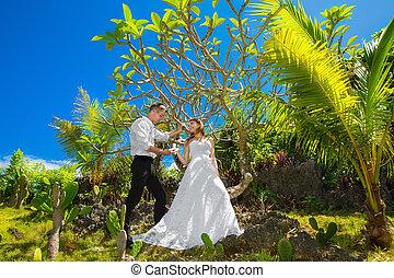 happy bride and groom having fun on a tropical garden under...