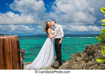 Happy bride and groom having fun on a tropical beach under...