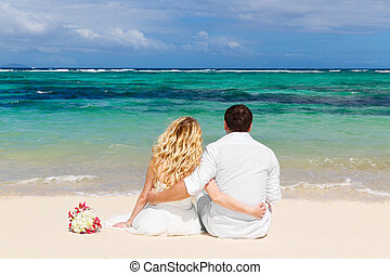 Bride and Groom having sitting on the tropical beach with...