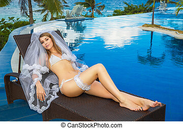 Beautiful young bride in a white bikini, veil and garter on...