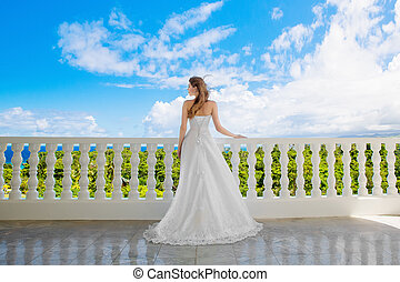 Happy bride standing next to the stone gazebo amid beautiful...