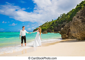 Happy Bride and Groom having fun on the tropical beach....
