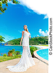 Beautiful bride in wedding dress with long train standing at...